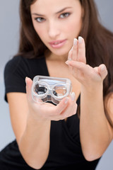 Woman holding contact lenses cases and lens; focus on container