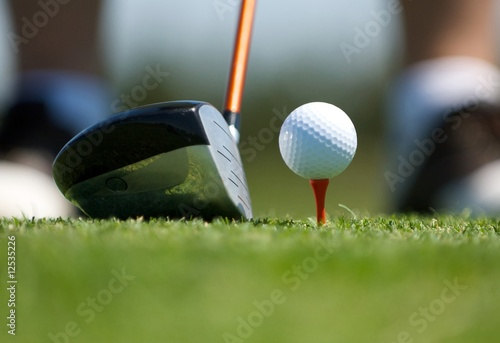 Up close image of a golf ball on tee with club - 12535226