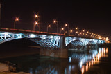 illuminated bridge piers over Vistula River by night - 12543680