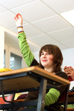 Jeune fille levant le bras en classe poster