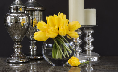 vase of yellow tulips with home decor accessories - tablescape