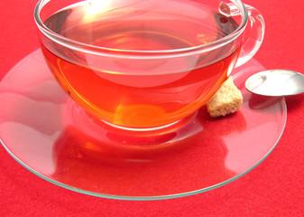 Teetasse mit Hagebuttentee auf rotem Tischset