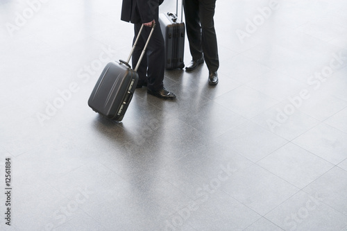 Two businessmen standing with suitcases