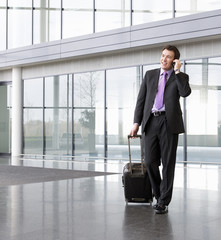 A businessman wheeling a suitcase, talking on a mobile phone