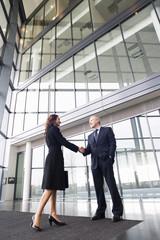 A businessman greeting a female client