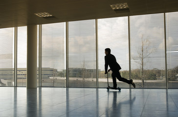 A businessman riding a scooter in an empty office
