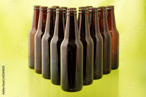 Empty beer bottles in front of a bright green background