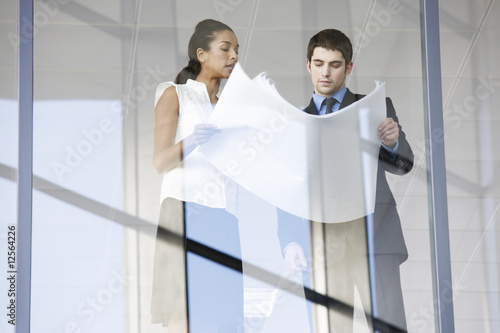 A businessman and woman discussing plans or blueprints