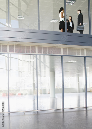 Three business colleagues on the upper floor on office building