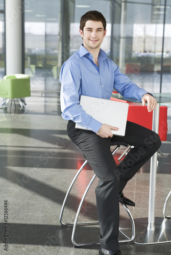 A businessman sitting in a modern office, holding some papers