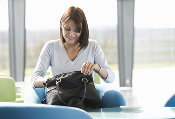 A woman sitting at a table, searching for an item in her handbag