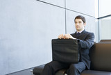 A young businessman in a waiting room holding a briefcase