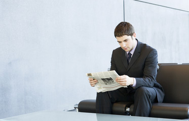 A young businessman in a waiting room reading a newspaper