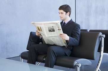 A young businessman in waiting room reading a newspaper