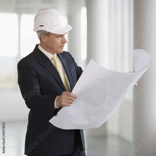 An architect wearing a hard hat holding plans