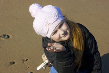 The girl shows the found cockleshell ashore