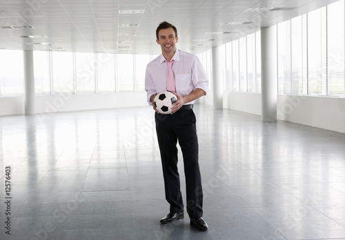 A businessman standing in empty office, holding a football