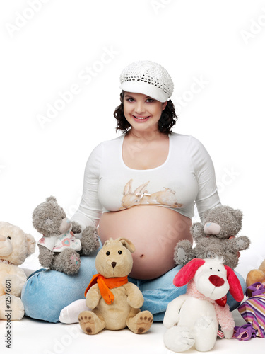 The pregnant woman sitting on a white background among toys.
