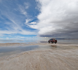 jeep in the salt lake salar de uyuni, bolivia