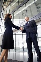 A businessman greeting female client