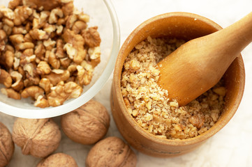 Walnuts: full, cracked and grinded. Focus on masher.