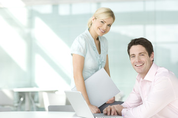 Two business colleagues at a laptop, smiling