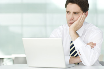 A businessman in an office sitting at laptop, looking bored