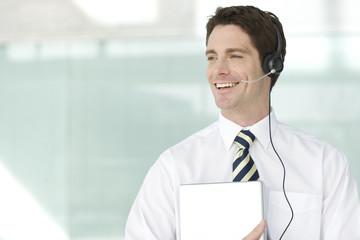 A man wearing a headset holding a folder
