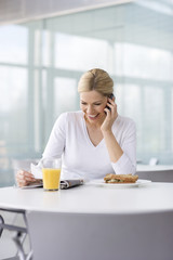 A woman in a cafe or office canteen, talking on a mobile phone