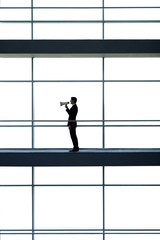 A businessman on office building, talking into a megaphone