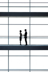 A businessman and woman on a walkway of office building,