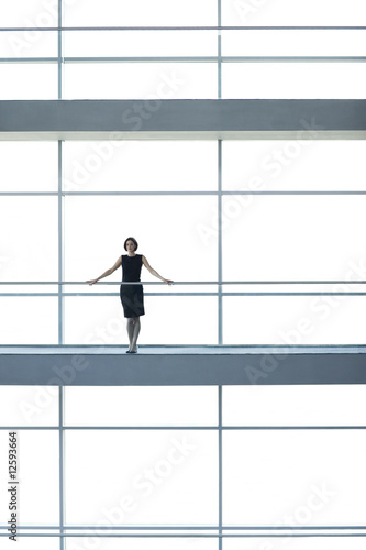 A businesswoman on a walkway of a large modern office building