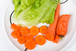 well-cut carrots and green vegetable on a white porcelain dish