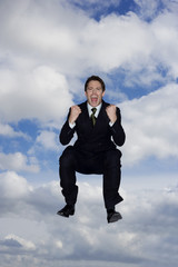 A businessman holding a briefcase, leaping in the air