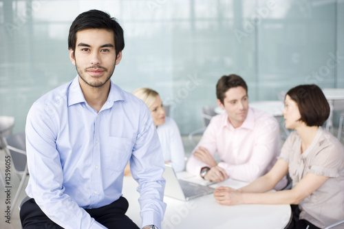 A businessman in office, three colleagues having a discussion