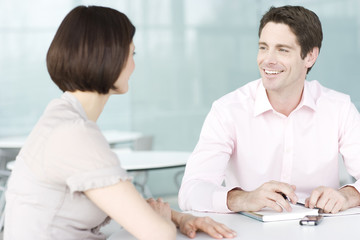 A businessman and woman having discussion in office, smiling