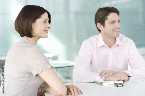 A businessman and woman sitting at a business meeting, smiling