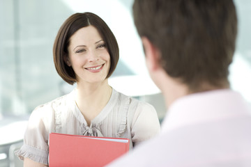 A businesswoman in an office, holding a red folder, smiling