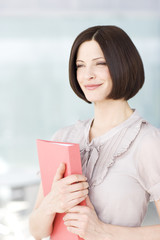 A blonde woman in an office, holding a red folder