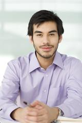 A portrait of a businessman sitting at a desk, smiling