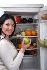 Woman take green apple from fridge