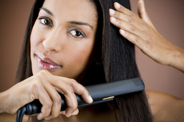 A young woman straightening her hair