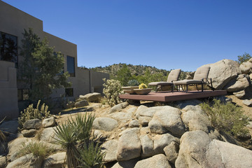 Deck on Rocks in Desert Landscape behind House