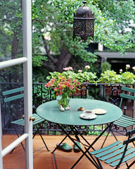 A cup of tea is served on the circular table in the balcony