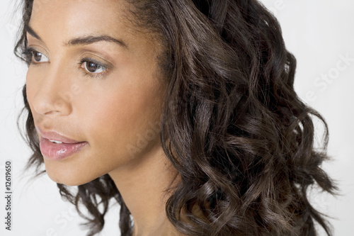 A portrait of a young black woman with long curly hair