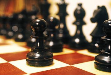 Close up of a pawn placed along with other chessmen on the chessboard