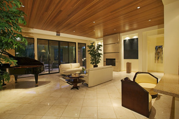 A spacious living room is seen with piano placed in one corner