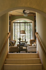 Armchairs in Front of Arched Window at Top of Stairs