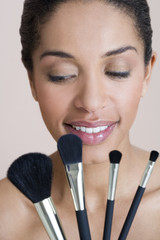 A woman holding four make-up brushes