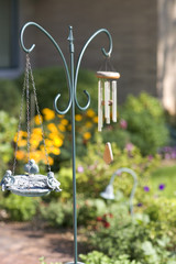 A wind chime and a carved object is hung on a stand in the garden